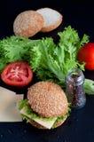 Hamburger with salad, tomato, meat on black  backdrop Royalty Free Stock Image