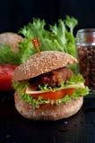 Hamburger with salad, tomato, meat on black  backdrop Stock Photos