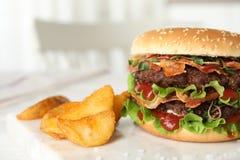 Hamburger saporito con bacon e le patate fritte sulla tavola, primo piano fotografia stock