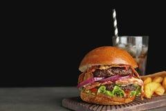 Hamburger saporito con bacon e le patate fritte sulla tavola Spazio per testo fotografie stock