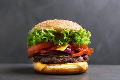 Hamburger saporito con bacon sulla tavola fotografia stock libera da diritti