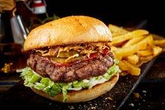 Hamburger saporito del manzo con ketchup ed il prosciutto fotografie stock