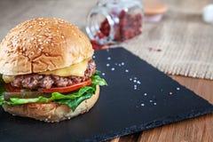 Hamburger saporito fresco con formaggio, lattuga, pomodoro, cetriolo sulla pietra nera con salsa Alimenti a rapida preparazione a immagine stock