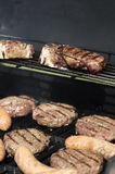 Hamburger, sausage and steak barbecued on the grill Royalty Free Stock Photo