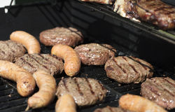 Hamburger, sausage and steak barbecued on the grill Royalty Free Stock Images