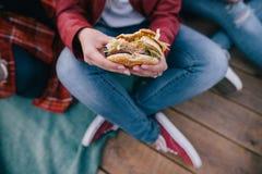 Hamburger savoureux chez des mains du ` s de la femme Nourriture industrielle à emporter Photo stock