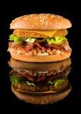 Hamburger savoureux de poulet sur un fond noir avec la réflexion photos stock