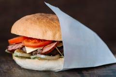 Hamburger savoureux frais enveloppé sur le livre blanc photos stock
