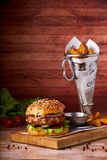 Hamburger served on wooden planks. Homemade hamburger with lettuce and cheese. Royalty Free Stock Images