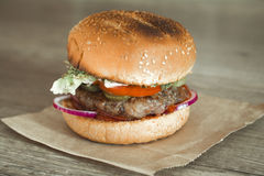 Hamburger on sesame buns with succulent beef patties and fresh salad ingredients  on crumpled brown paper on a rustic wood table Royalty Free Stock Image