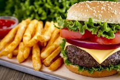 Hamburger on sesame seed bun with fries. Thick and juicy hamburger on sesame seed bun with lettuce, tomato, onions and slic of cheese with order of fries royalty free stock images