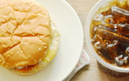 Hamburger and soda with ice in plastic cup Stock Photos