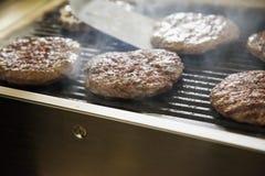 Hamburger sopra la griglia immagini stock