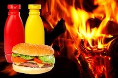 Hamburger sopra una priorità bassa delle fiamme Immagini Stock Libere da Diritti