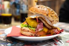 Hamburger speciale con bacon e l'uovo su un piatto fotografia stock libera da diritti