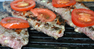 Hamburger steak and tomatoes on a grill Stock Photo