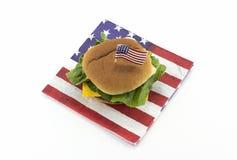 Hamburger su un tovagliolo e sugli stuzzicadenti della bandiera americana Fotografia Stock Libera da Diritti
