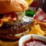 Hamburger succoso con il formaggio, il bacon, le fritture, il ketchup e la birra di gorgonzola fotografia stock libera da diritti