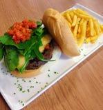 Hamburger succoso con il razzo, il pomodoro e le fritture fotografie stock