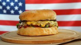 Hamburger succoso fresco che gira sul fondo della bandiera degli Stati Uniti archivi video