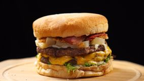 Hamburger succoso fresco che gira sul fondo nero video d archivio