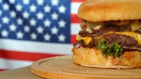 Hamburger succoso fresco con formaggio, salsa e le verdure giranti su un bordo di legno davanti alla bandiera americana stock footage