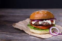 Hamburger succoso su fondo di legno Fotografie Stock