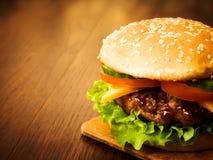 Hamburger succoso su un bordo di legno Immagini Stock