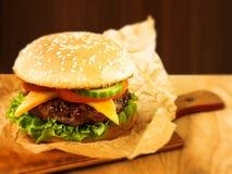 Hamburger succoso su un bordo di legno Immagini Stock Libere da Diritti