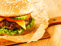 Hamburger succoso su un bordo di legno Fotografia Stock