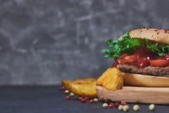 Hamburger suculento caseiro com legumes frescos e cunhas da batata com especiarias Na mesa Vista horizontal Copie o espaço imagens de stock royalty free