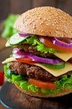 Hamburger suculento grande com vegetais em um fundo de madeira Imagens de Stock Royalty Free