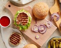 Hamburger sul bordo di legno con la cipolla ed i pomodori fotografia stock libera da diritti