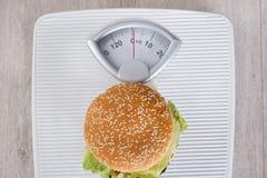 Hamburger sur l'échelle de poids Image stock