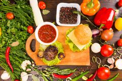 Hamburger Surrounded by Fresh Veggies and Toppings Stock Photos