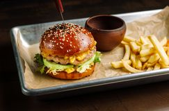 Hamburger with tavern. Lies on aluminum cuvettes. royalty free stock photography