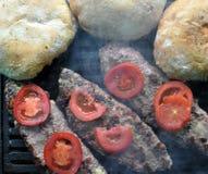 Hamburger, Tomaten und Brot auf Grill Stockbilder