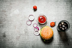 Hamburger with tomato ketchup and soda on stone table. Stock Images