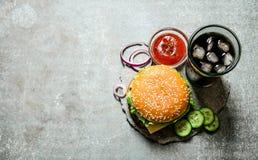 Hamburger with tomato ketchup and soda on stone table. Stock Photo