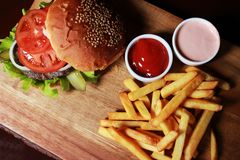 Hamburger with tomatos, onion, salad leaves, salted cucumber and Royalty Free Stock Photo