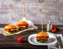 Hamburger und Fische auf einem Holztisch Lizenzfreies Stockbild