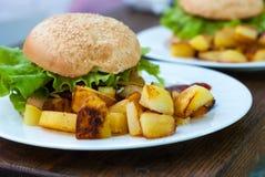 Hamburger und gebratene Kartoffeln auf einer weißen Platte lizenzfreie stockbilder