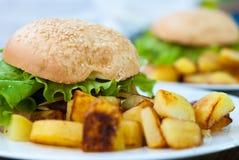 Hamburger und gebratene Kartoffeln auf einer weißen Platte stockfotos