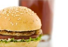 Hamburger und Glas mit Getränk Stockfotografie