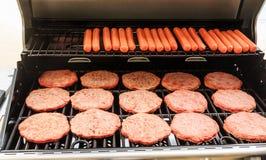 Hamburger und Hotdoge auf Grill lizenzfreie stockfotos
