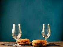 Hamburger und leere Gläser stockbilder