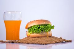 Hamburger und orain Saft auf weißem Hintergrund, Hamburger fokussieren O Stockfotografie