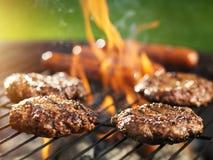 Hamburger und Würstchen, die auf loderndem Grill kochen Stockfotografie