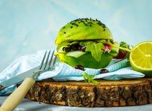 Hamburger végétarien d'avocat avec des haricots noirs et des légumes Photo libre de droits