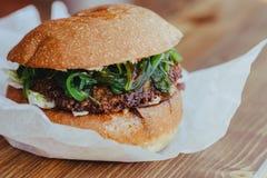 Hamburger v?g?tarien fait maison frais d?licieux de fromage avec des anneaux de salade, de fromage, de tomates, de laitue et d'oi images libres de droits